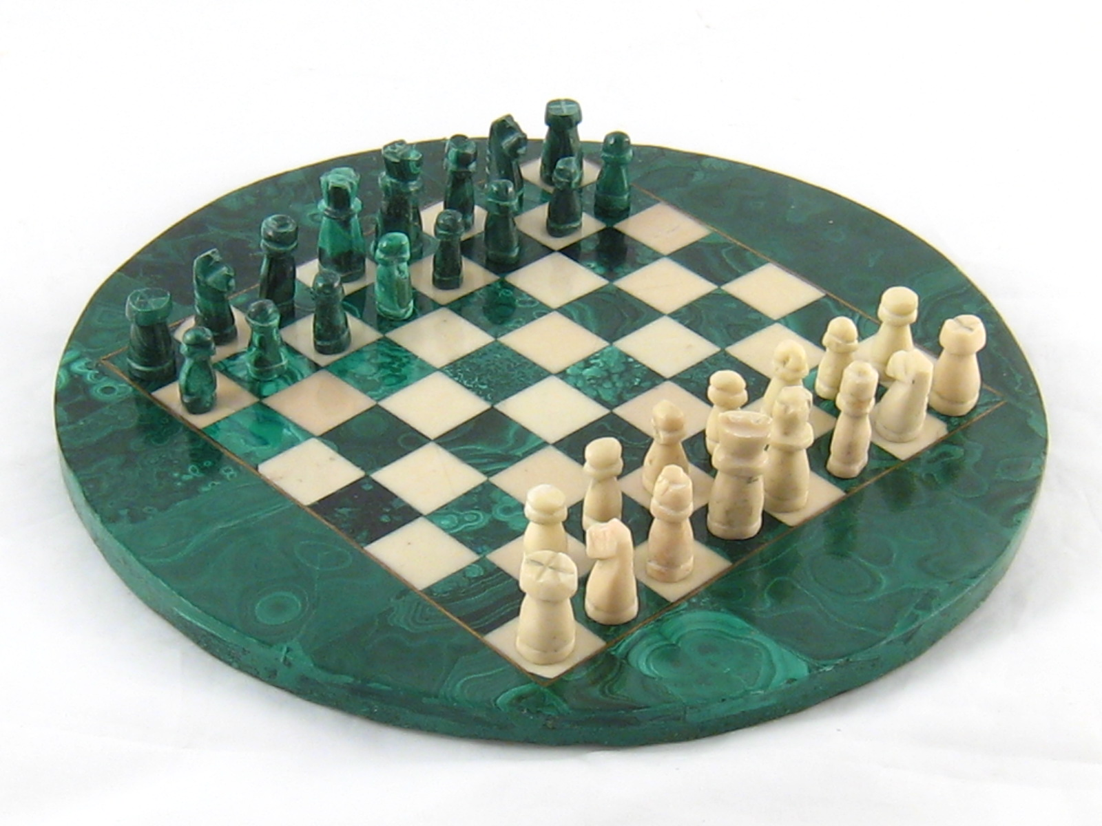 Lot 505 - A circular green and white chess set and board.