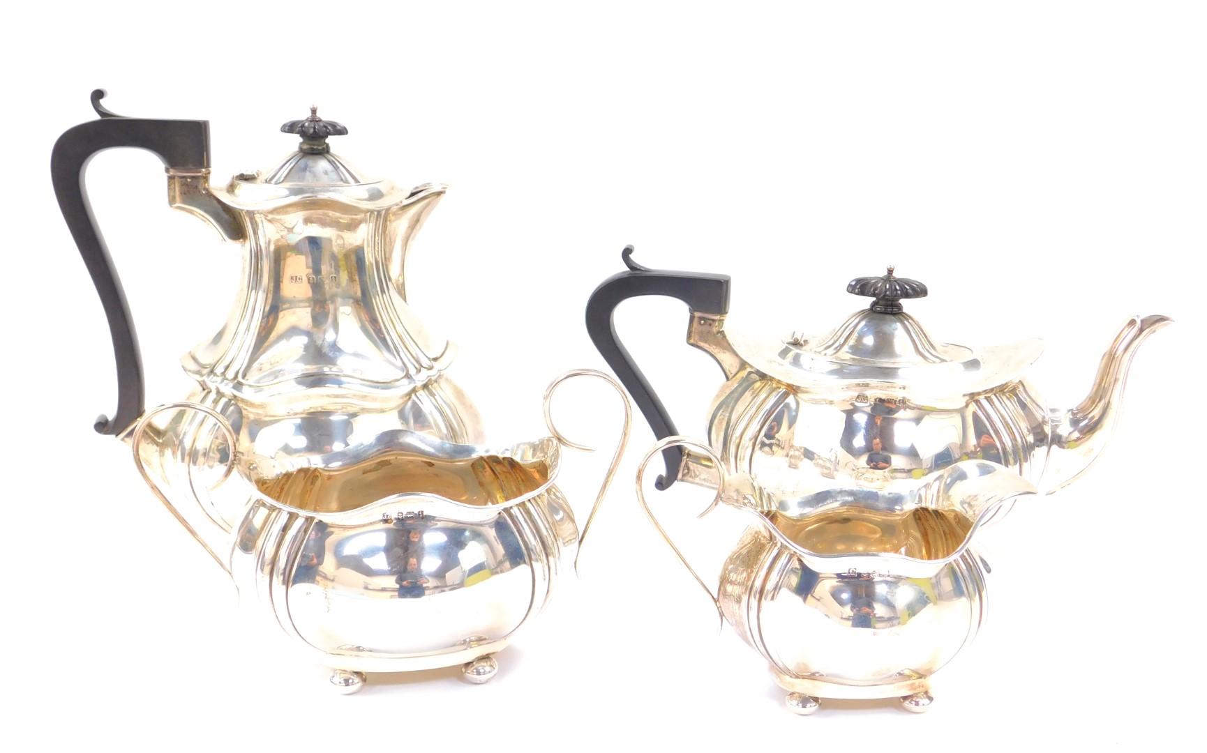 Lot 6 - An Edward VII silver four piece tea set, of lobed and fluted form, raised on four bun feet,