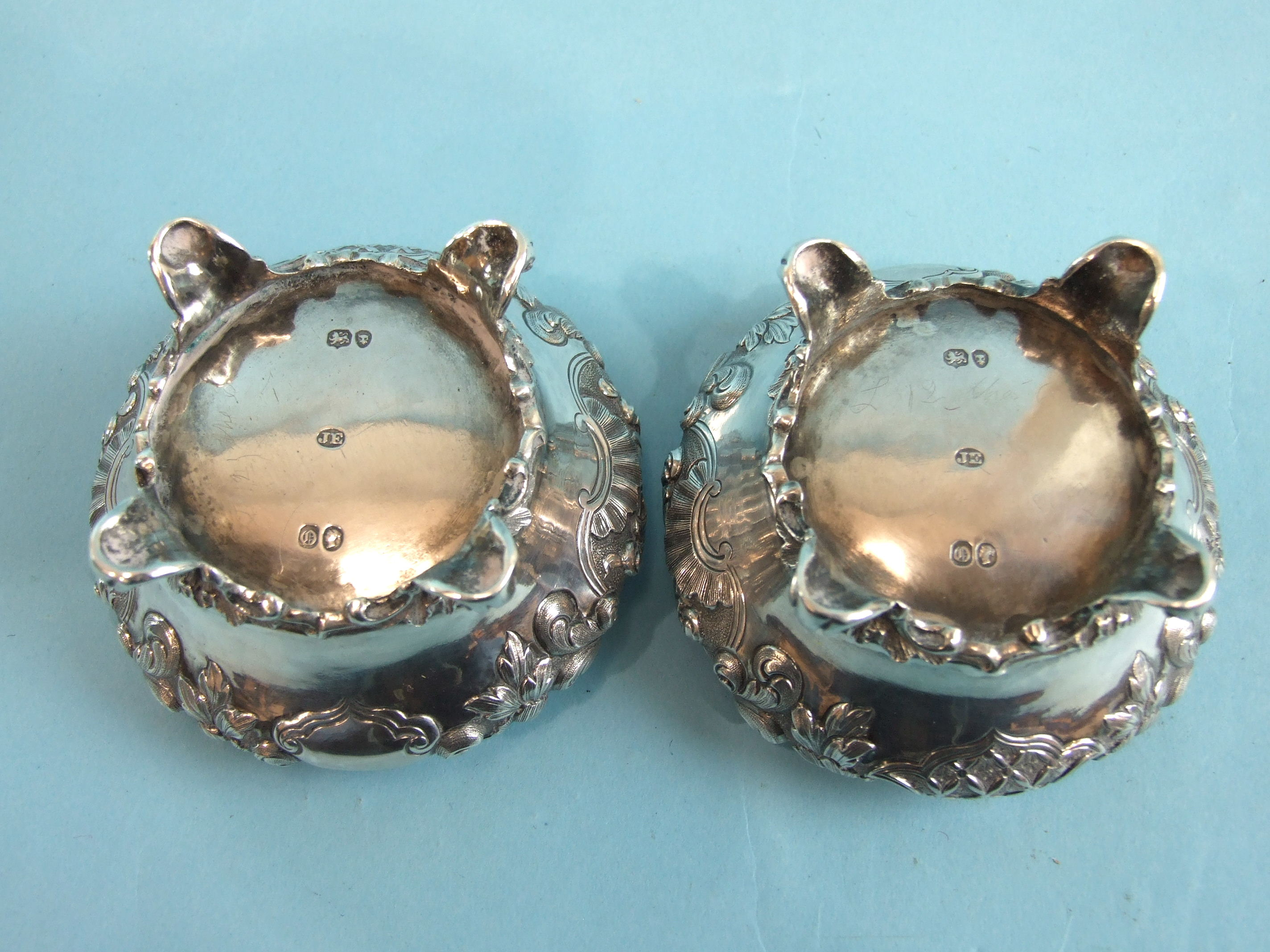 A pair of Victorian salts of compressed circular form embossed with flowers and foliage, on four - Image 2 of 4