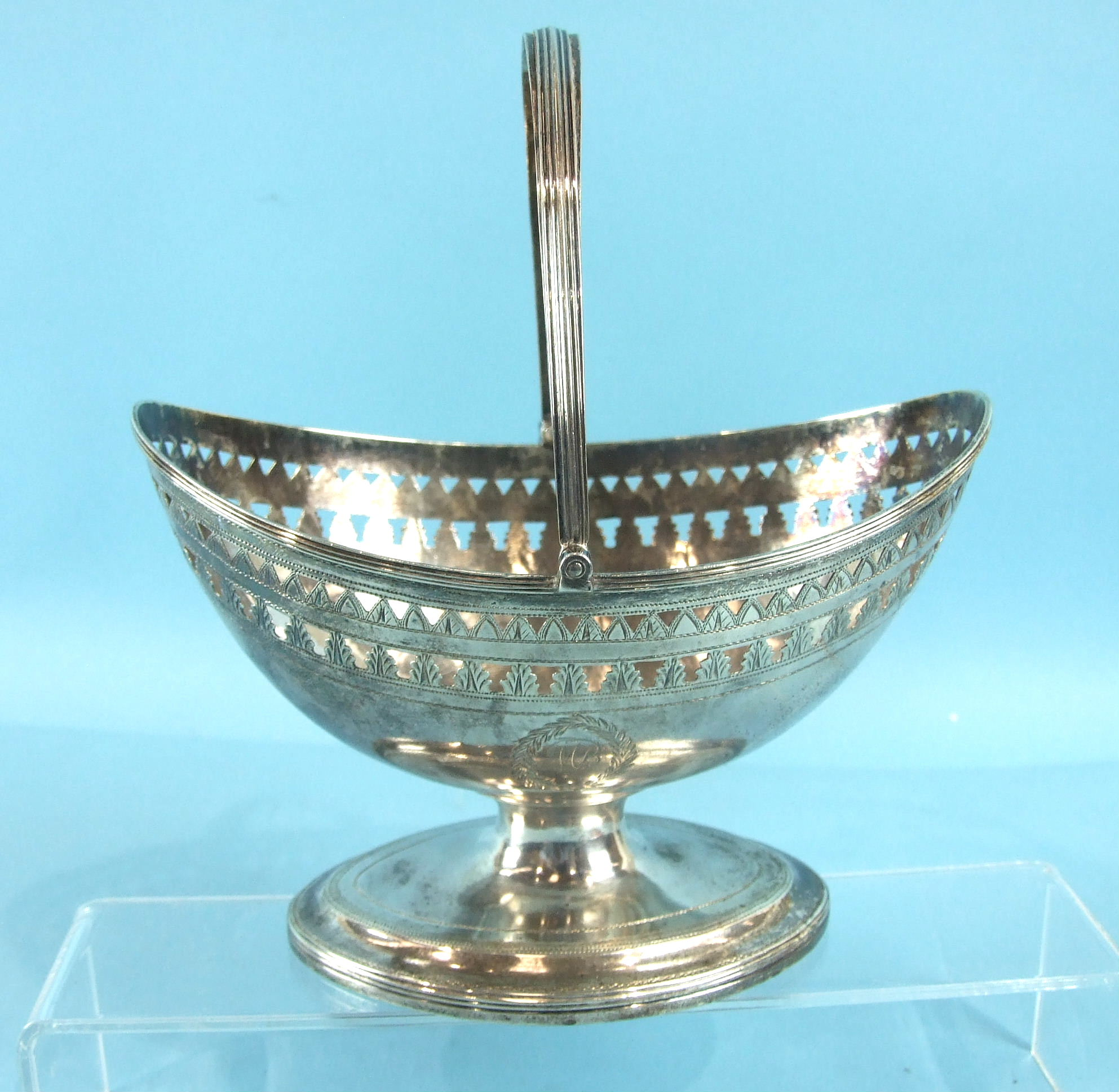 Lot 331 - A George III Newcastle boat-shaped sugar basin with reeded swing handle and borders, the body having