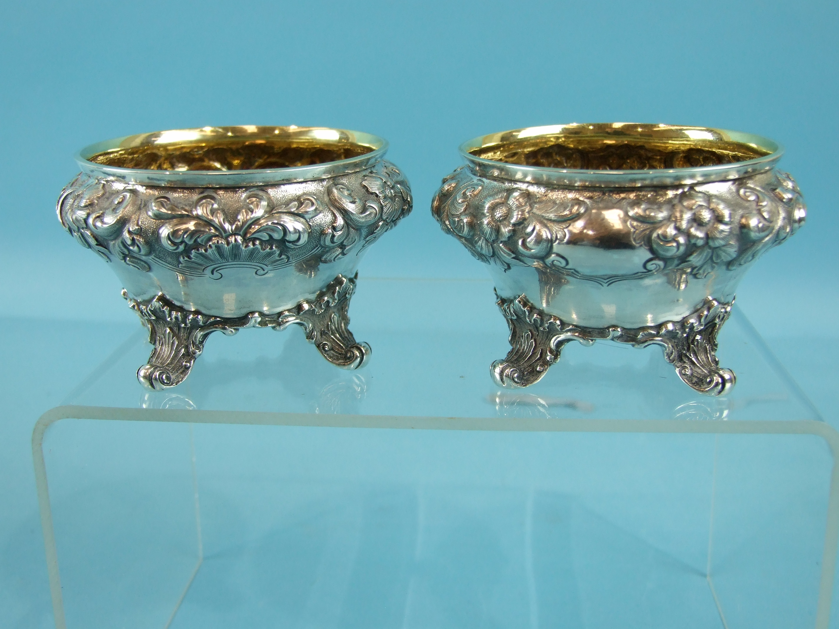 A pair of Victorian salts of compressed circular form embossed with flowers and foliage, on four