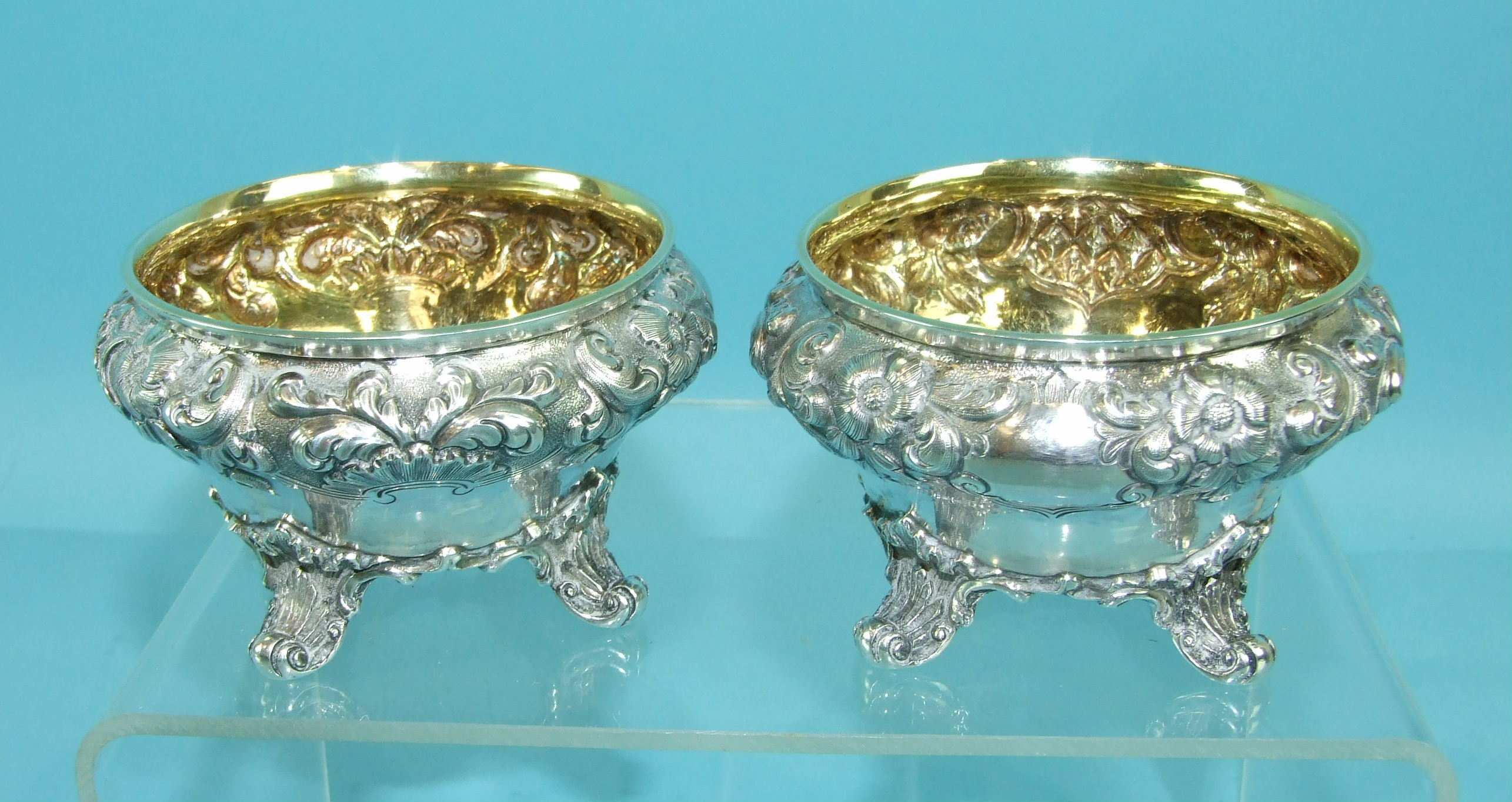 A pair of Victorian salts of compressed circular form embossed with flowers and foliage, on four - Image 3 of 4