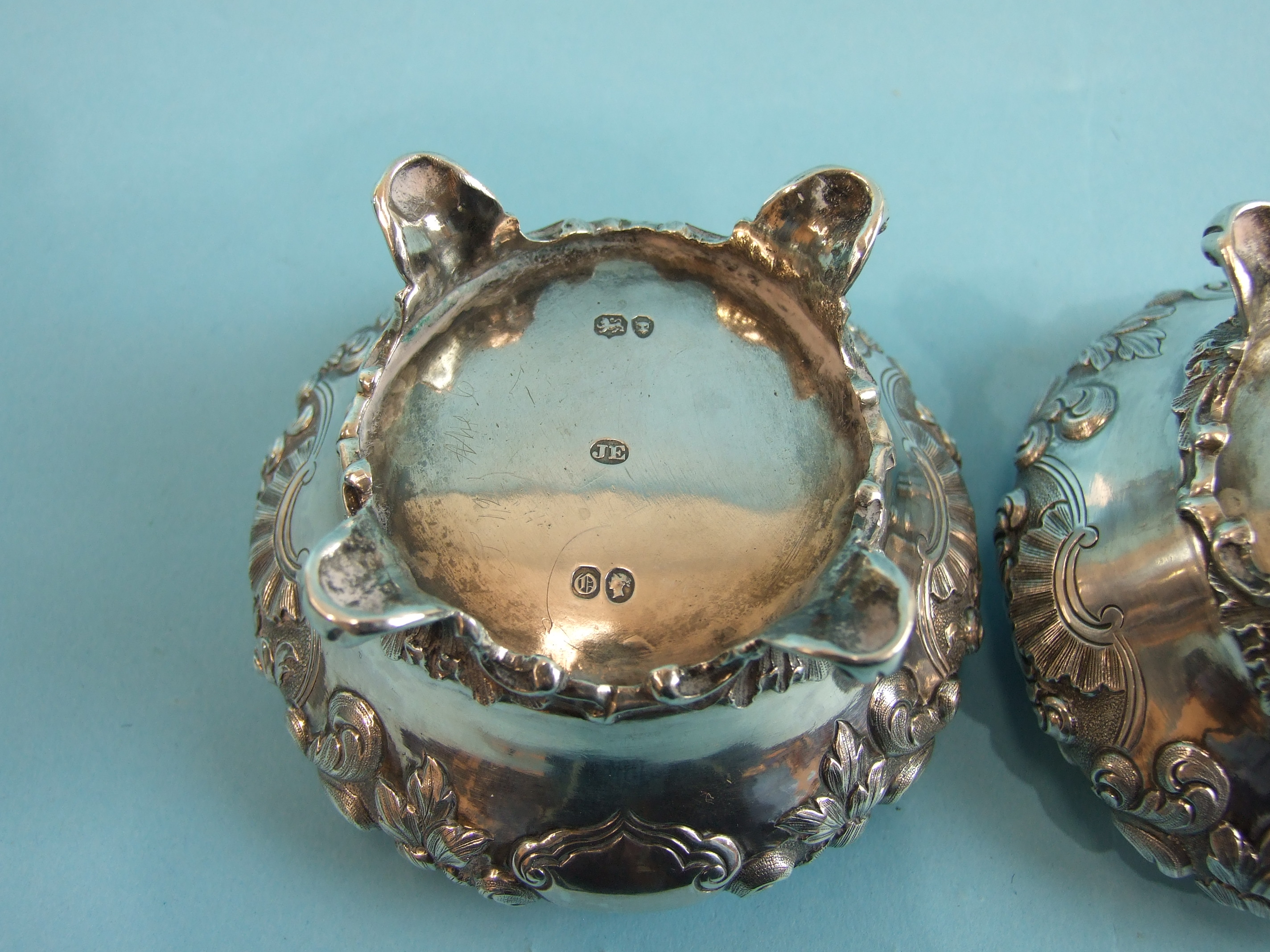 A pair of Victorian salts of compressed circular form embossed with flowers and foliage, on four - Image 4 of 4