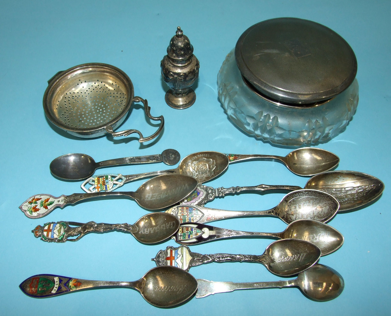 A silver tea strainer, Birmingham 1937, a silver-topped powder jar, ten sterling silver souvenir