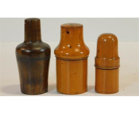 A collection of three treen apothecary's bottle holders with turned screw tops and with their original bottles. H.14cm (talle