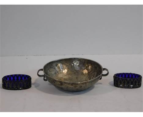 A white metal Arts and Crafts hammered design bowl/porringer with twin scrolling design handles along with two silver pierced