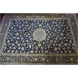 A Persian Kashan carpet the central floral medallion surrounded by floral swags and motifs, on a