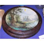 """A pair of late 19th century landscape decorated pottery wall plaques, 14"""" dia, in walnut frames"""