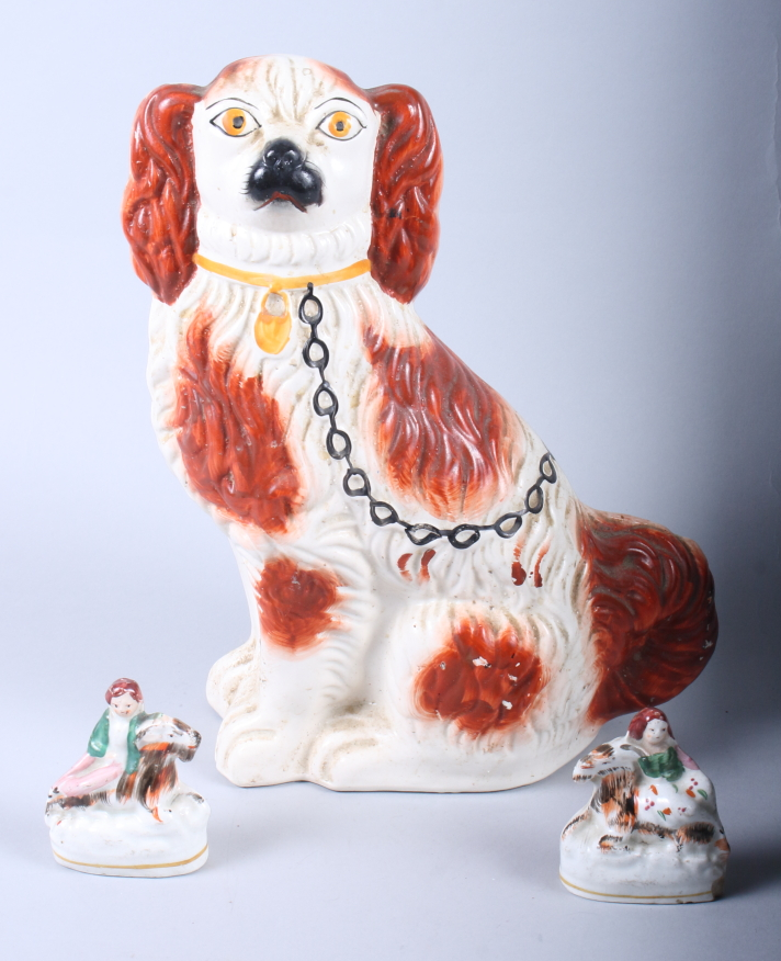 "Lot 15 - A 19th century Staffordshire spaniel, 12"" high, and a pair of 19th century Staffordshire figures,"