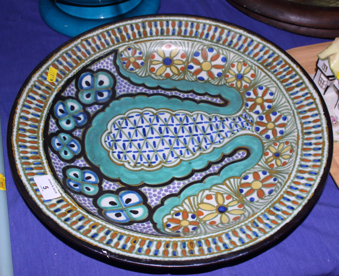 "Lot 5 - A mid 20th century Gouda pottery charger, richly painted with flowers and abstract pattern, 17"" dia,"