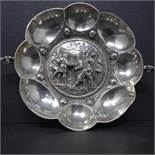 A late 19th century German silver wine taster, of lobed form with the centre repousse embossed