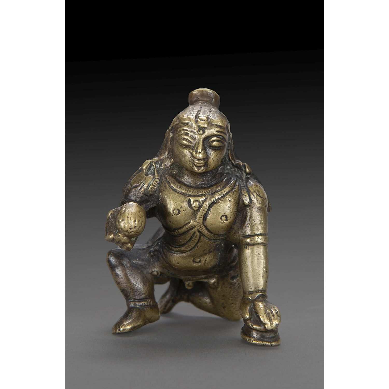 PETIT SUJET en bronze patiné, représentant Krishna agenouillé, la main gauche appuyée sur une