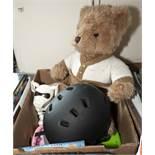 A bike helmet, teddy bear and other toys