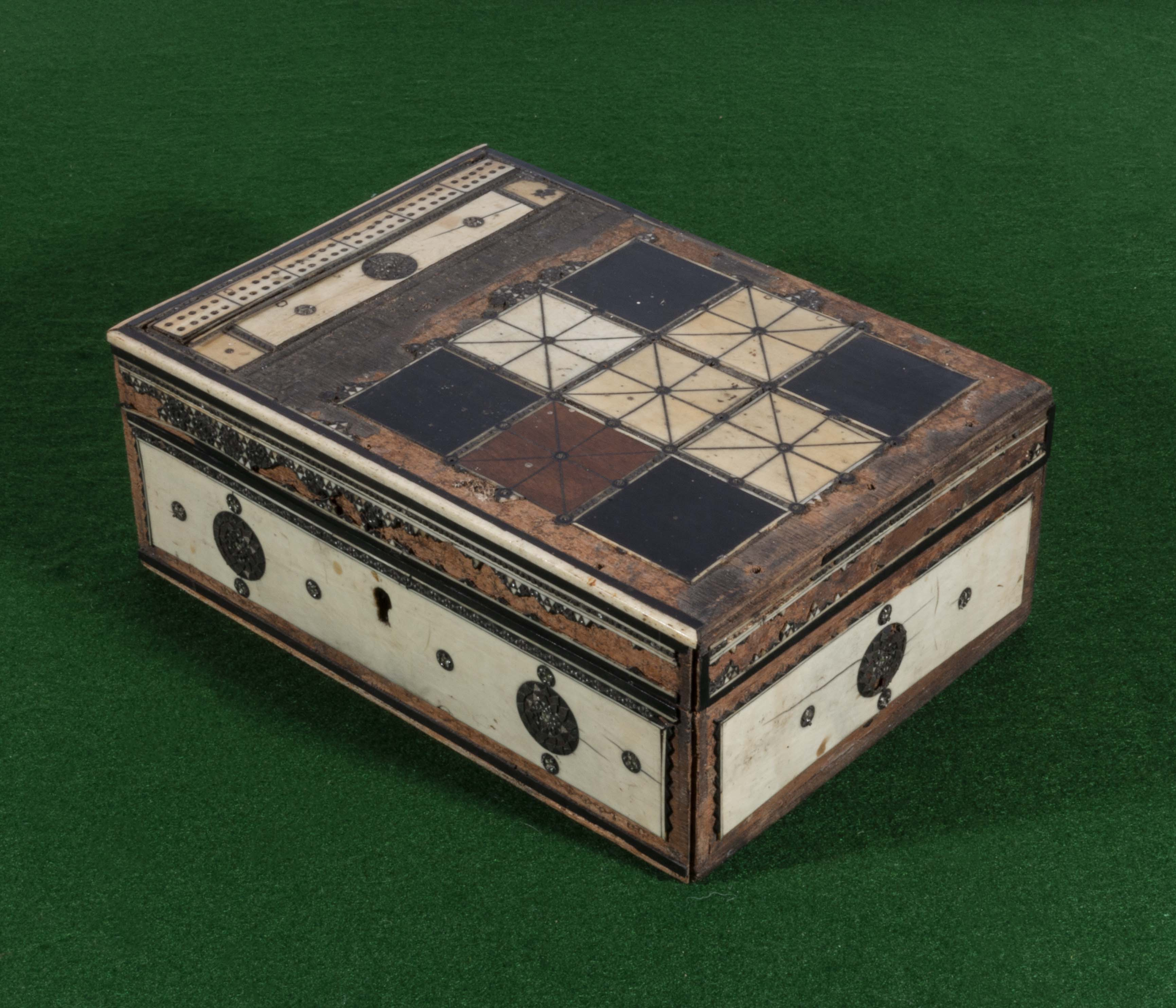 Lot 54 - An old box containing vintage draught pieces
