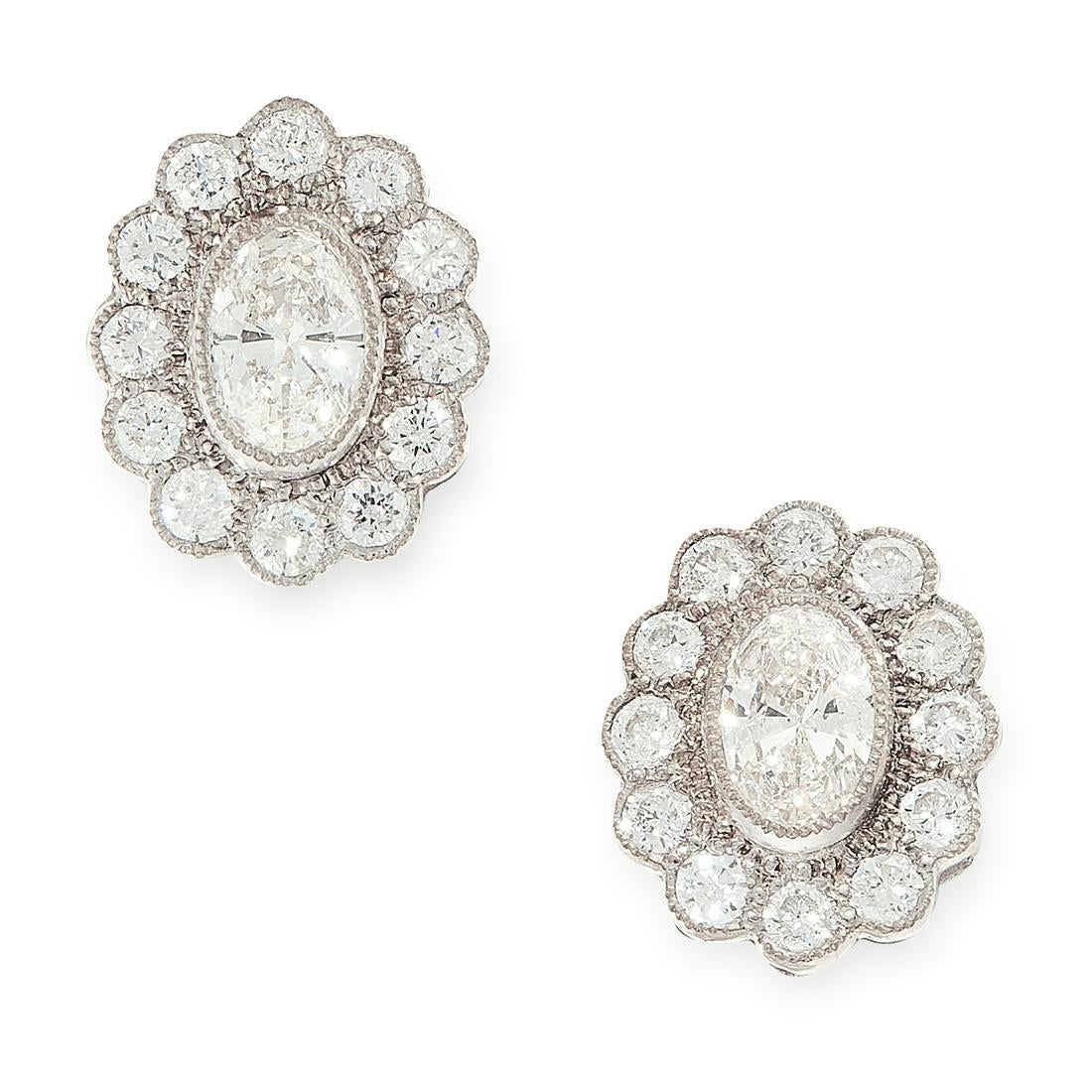 A PAIR OF DIAMOND CLUSTER STUD EARRINGS in 18ct white gold, each set with an oval cut diamond within