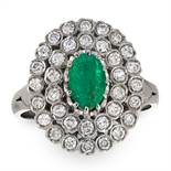 AN EMERALD AND DIAMOND CLUSTER RING in 18ct white gold, set with an oval cut emerald in a two row