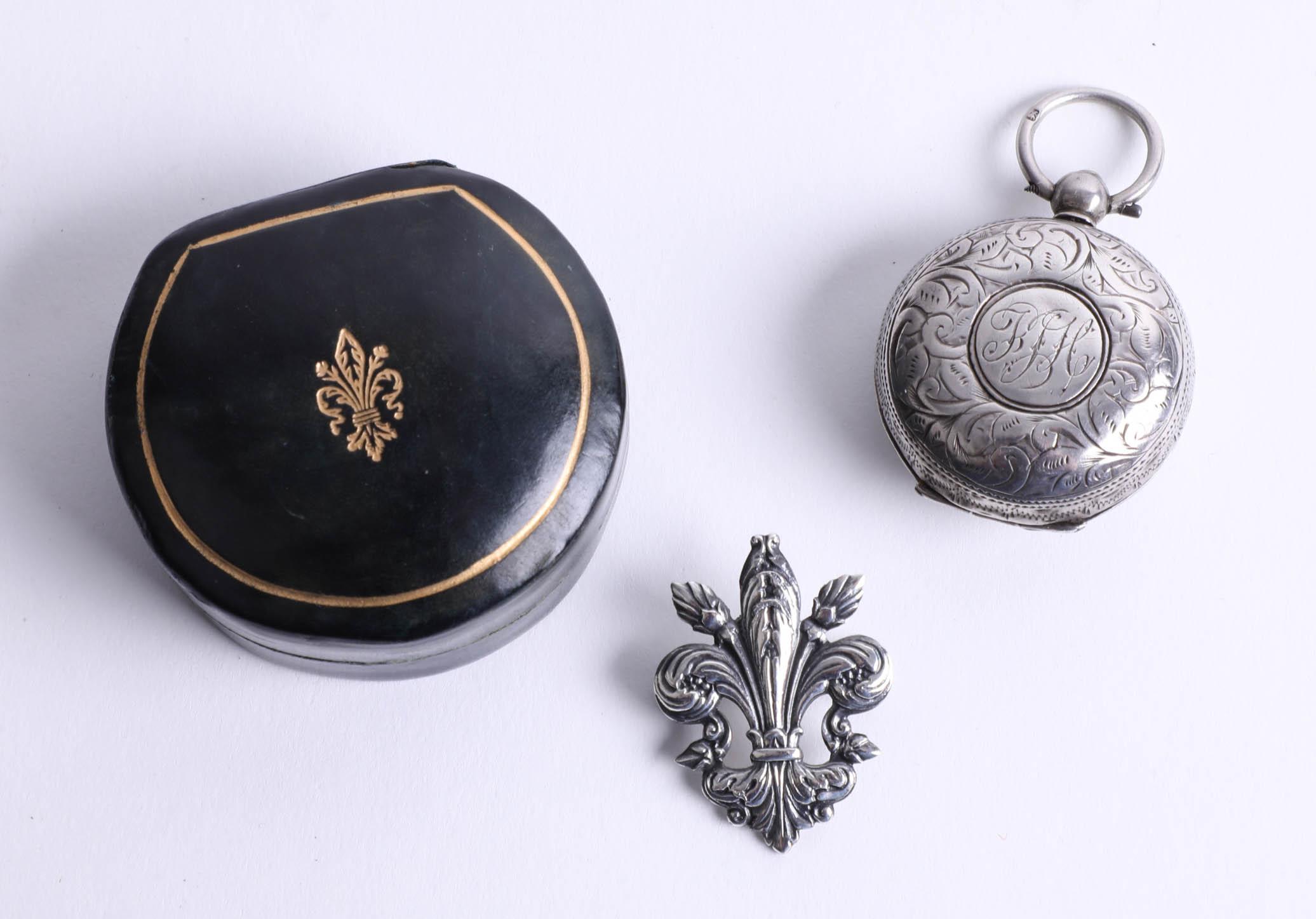 A Victorian silver sovereign holder and a fleur-de-lis medallion with box (2).