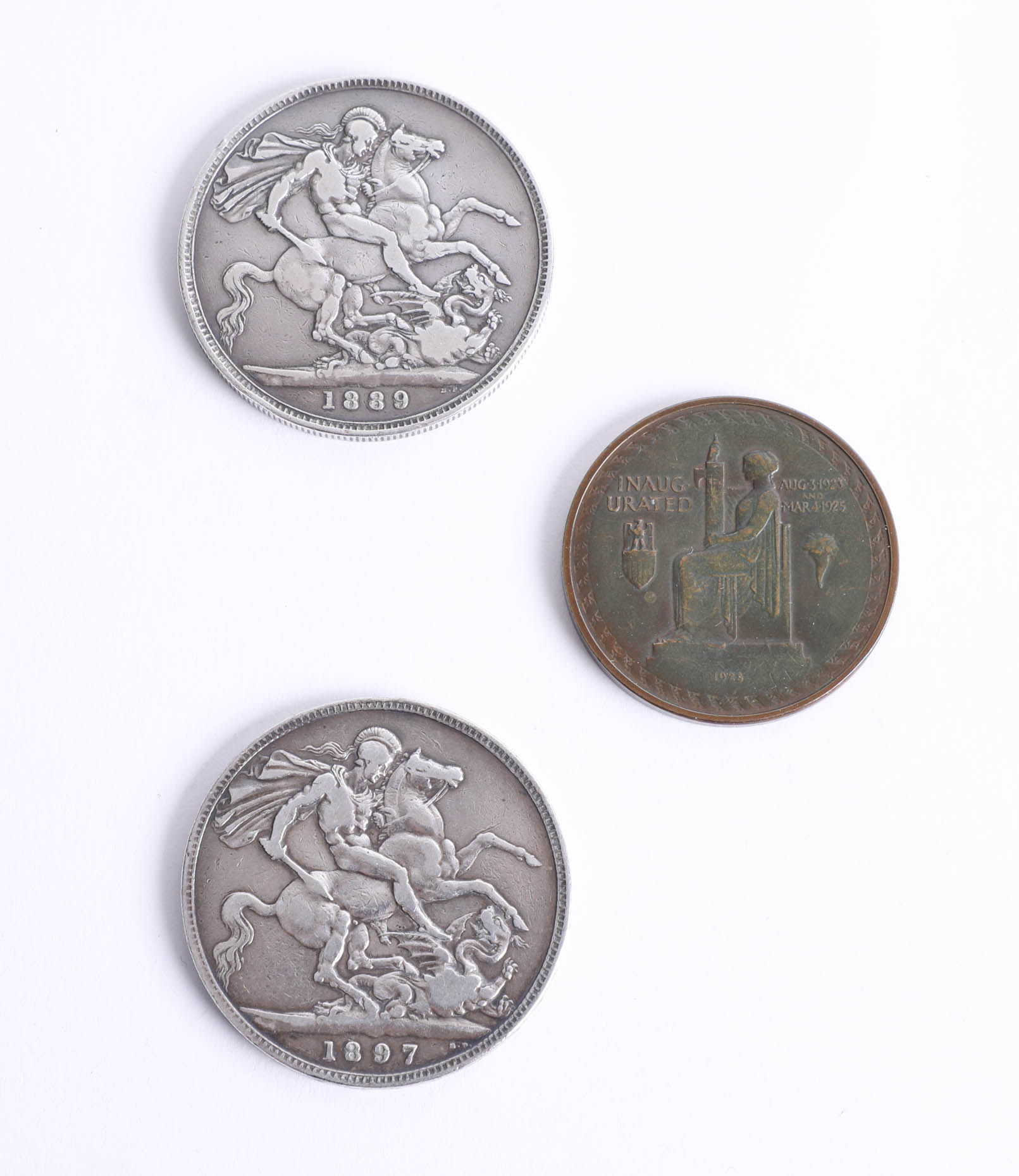 Two Victorian silver crowns dated 1889 and 1897 together with a 1928 Calvin Coolidge coin (3).