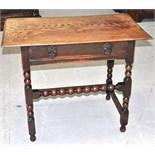 An Edwardian two drawer oak table on turned legs.