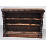 A Victorian oak two shelf bookcase with carved figures to either side and a heavily carved frieze