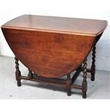 An early 20th century oak drop leaf table on barley twist supports,