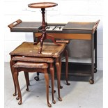 A small round side table a retro hostess trolley on ball feet and a nest of three walnut tables