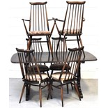 An Ercol dining suite comprising dark oak table and six matching stick back chairs (4+2),