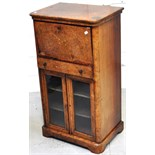 A 19th century walnut writing bureau above glazed music cabinet with central drawer and inlaid