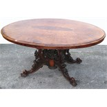 A Victorian oval walnut dining table of small proportions on heavily carved base decorated with