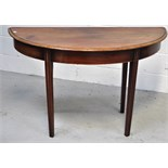 An early 19th century mahogany demi lune side table on tapering fluted supports, length 109cm.