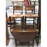 An early 20th century oak drop leaf table with barley twist supports,