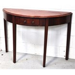 An early 20th century mahogany demi-lune table raised on fluted legs with central single drawer,