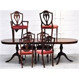 A reproduction mahogany extending dining table on two tripod supports with single extending leaf,