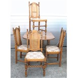 A pale oak drop leaf dining table on barley twist supports and four dining chairs with bergère