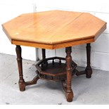 An early 20th century oak octagonal occasional table with lower shelf and raised on ring turned