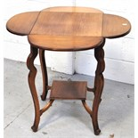 A 20th century oak drop leaf occasional table with lower shelf and raised on incised outswept