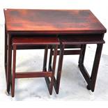 A nest of three 1960s rosewood tables, largest on wheels, width 74cm.