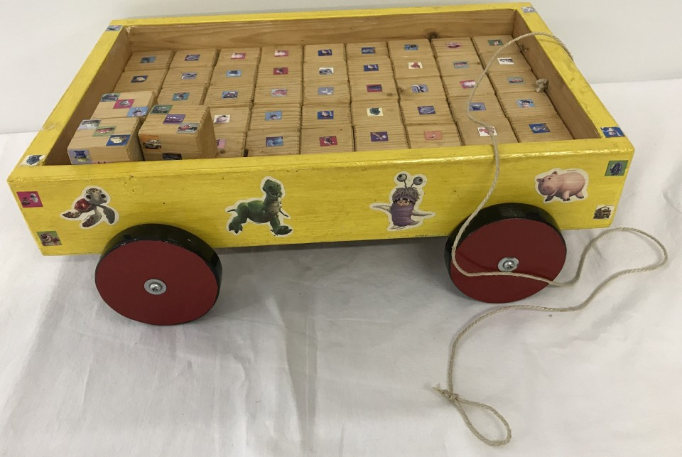 Lot 43 - A wooden pull along child's trolley filled with wooden blocks decorated with Disney stickers.