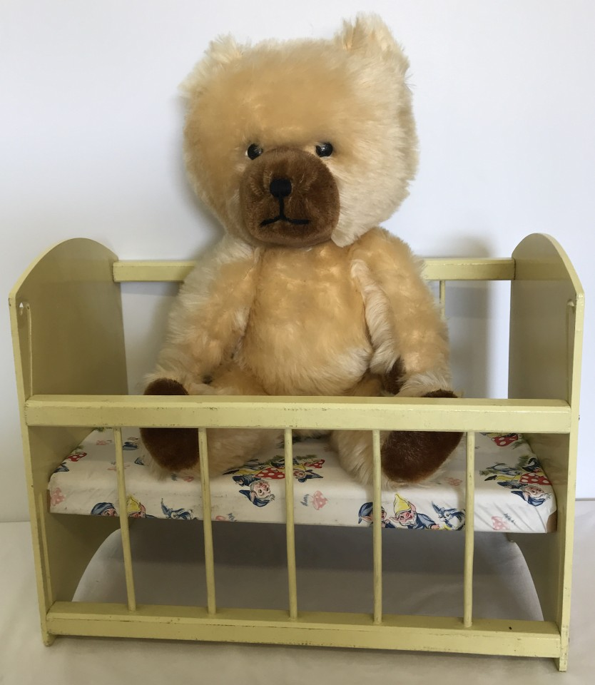 Lot 129 - A 1950's Blonde Schuco nursery bear together with a vintage wooden toy dolls cot.
