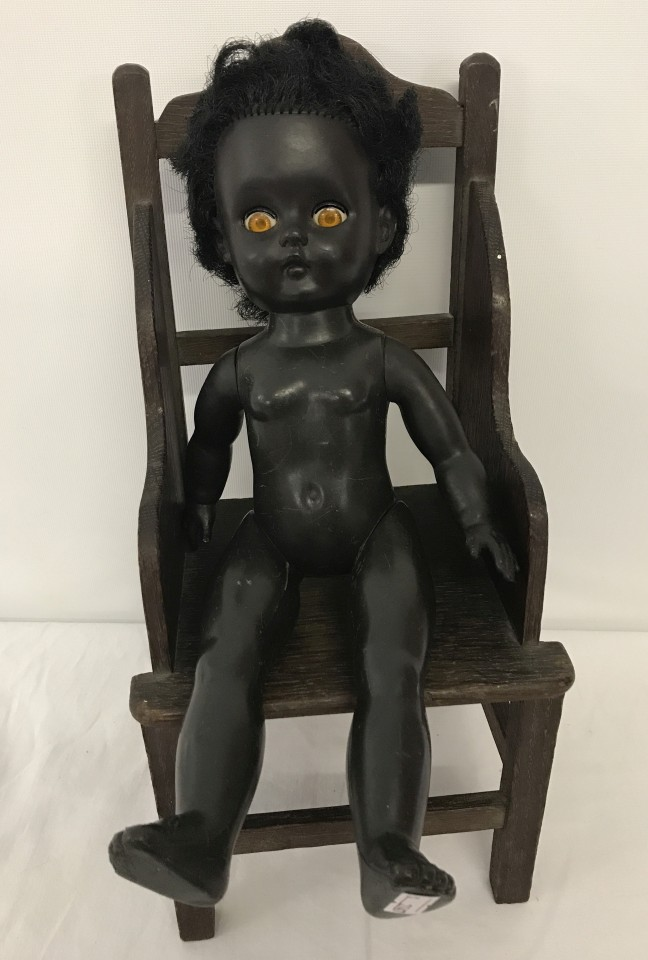 Lot 126 - An English made black vinyl doll together with a dolls wooden chair.
