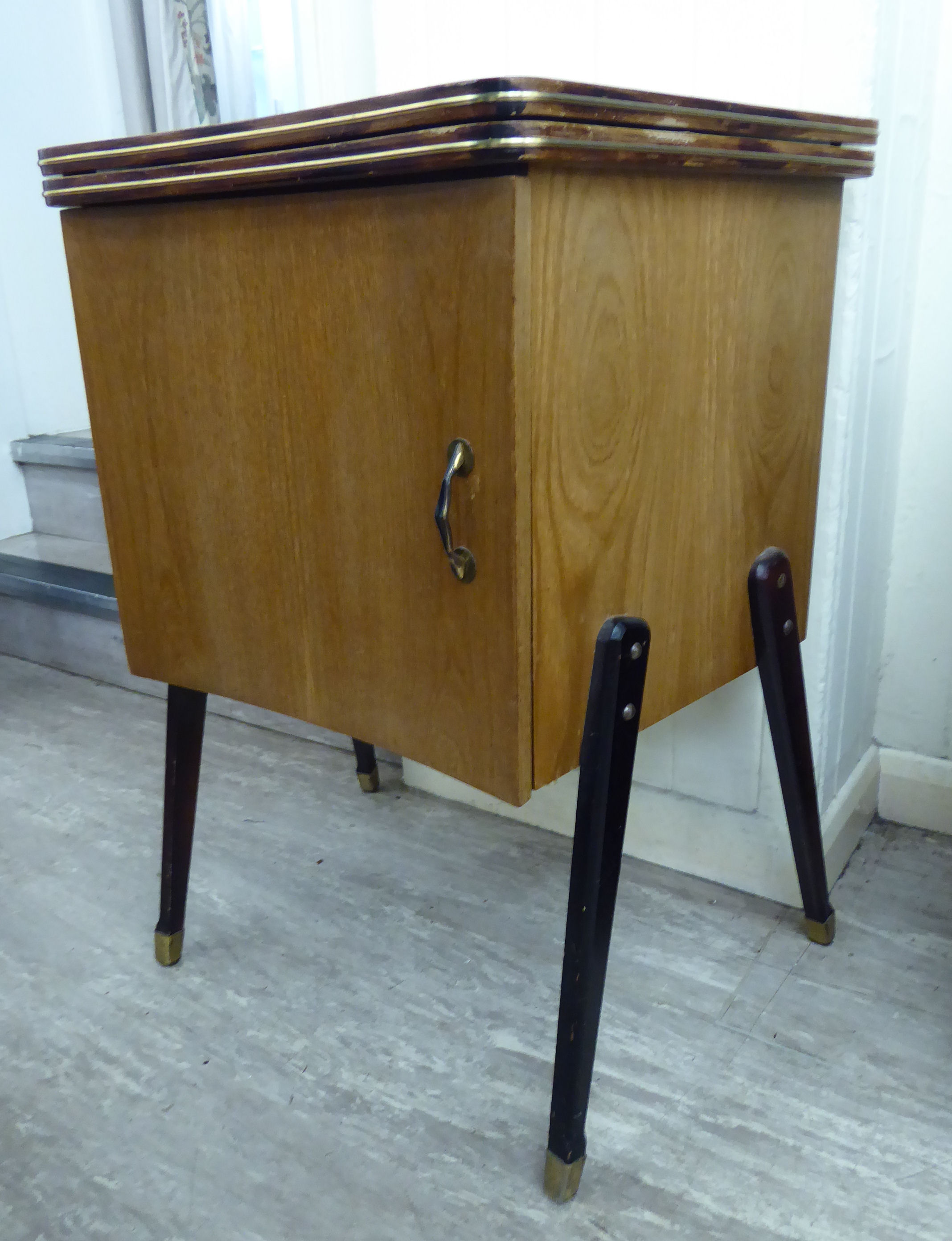 Lot 18 - A 1960s teak finished cabinet with a rising table top and a cupboard,