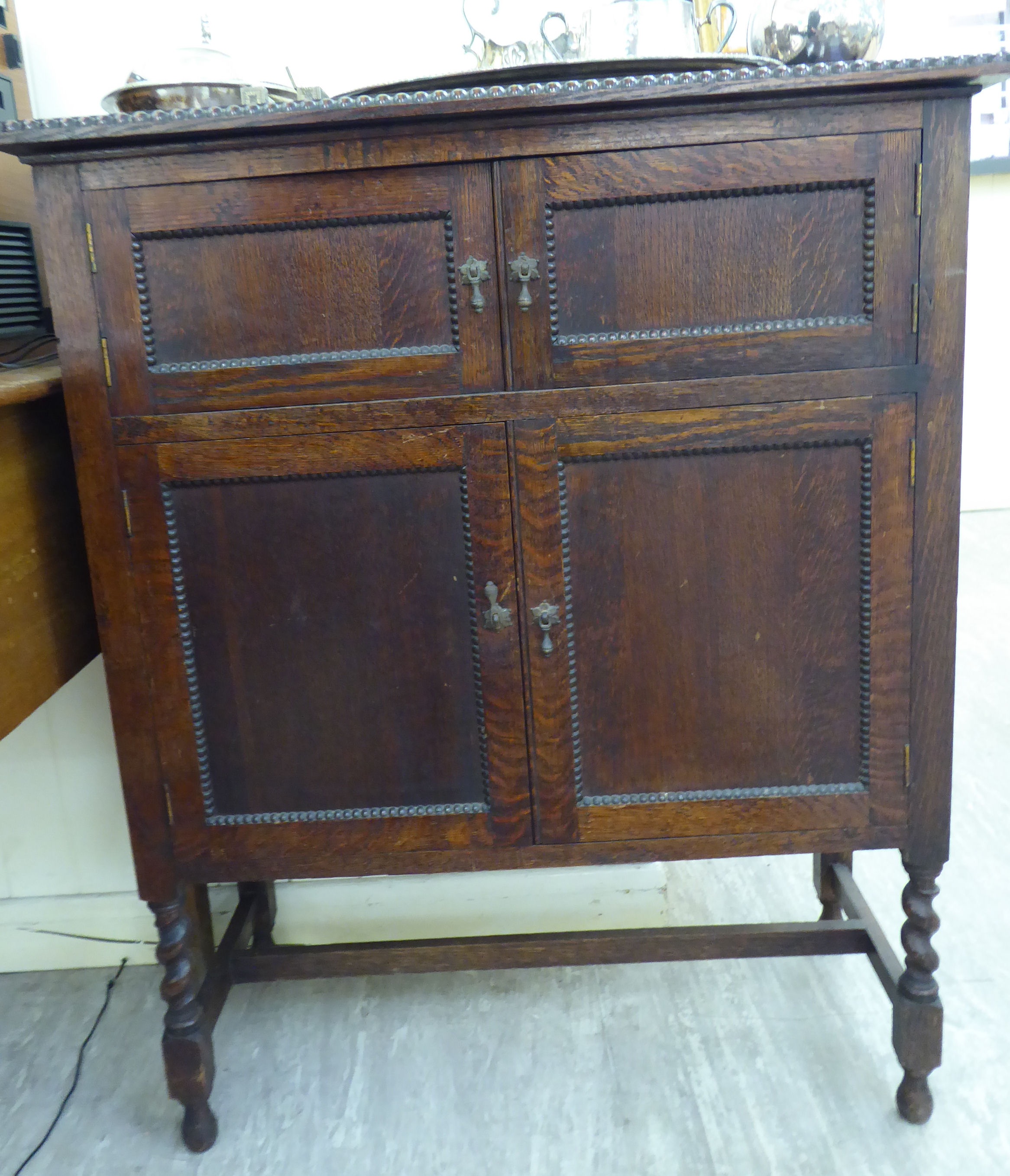 Lot 9 - A 1920s carved bead bordered oak side cabinet, enclosed by two pairs of panelled doors,