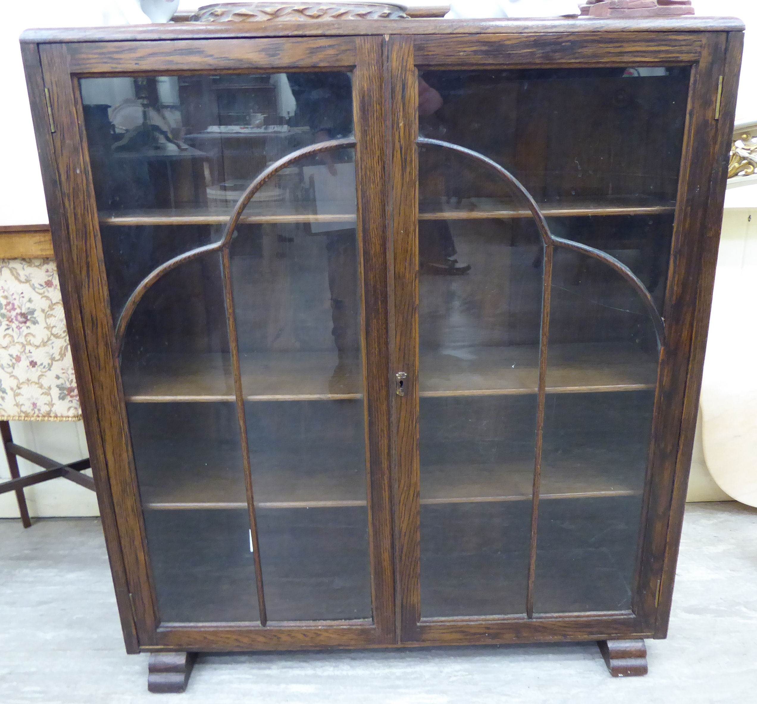 Lot 7 - A 1930s oak display cabinet, enclosed by a pair of full-height, glazed panelled doors,