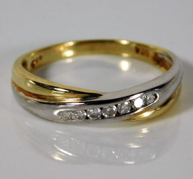 Lot 320 - A 9ct two colour gold ring set with 0.15ct diamond