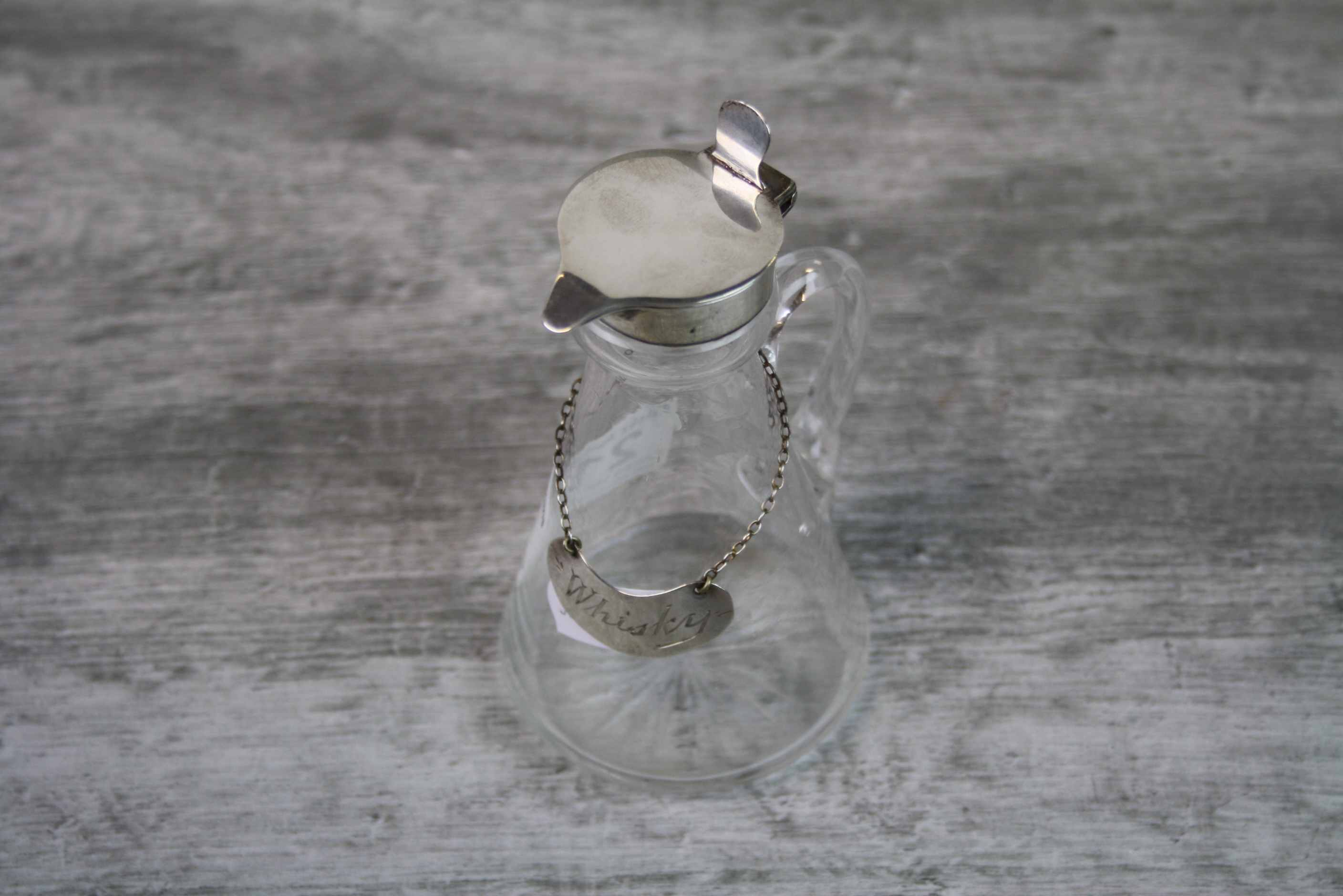 Edwardian silver topped whisky noggin, glass body of plain form with cut glass star design to