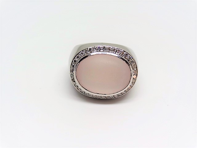 Lot 6 - Modern coktail ring with a milky rose quartz in halo design set in 18k white gold. 40 diamonds. Size