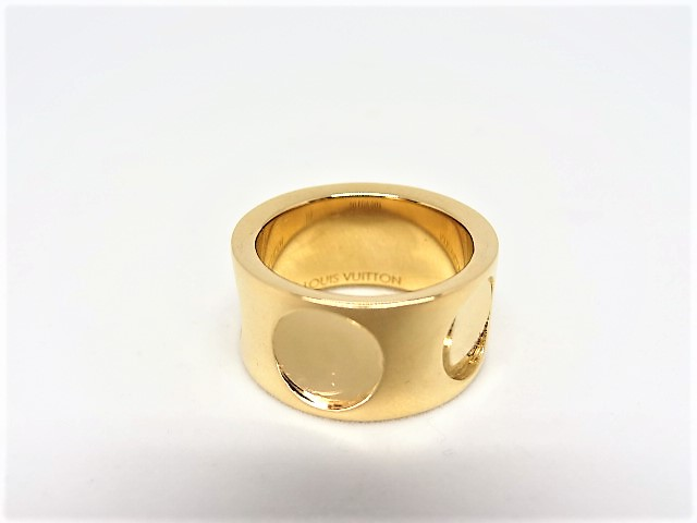 Lot 19 - Louis Vuitton band style ring composed of 18k Yellow Gold and prominently featuring a LOUIS