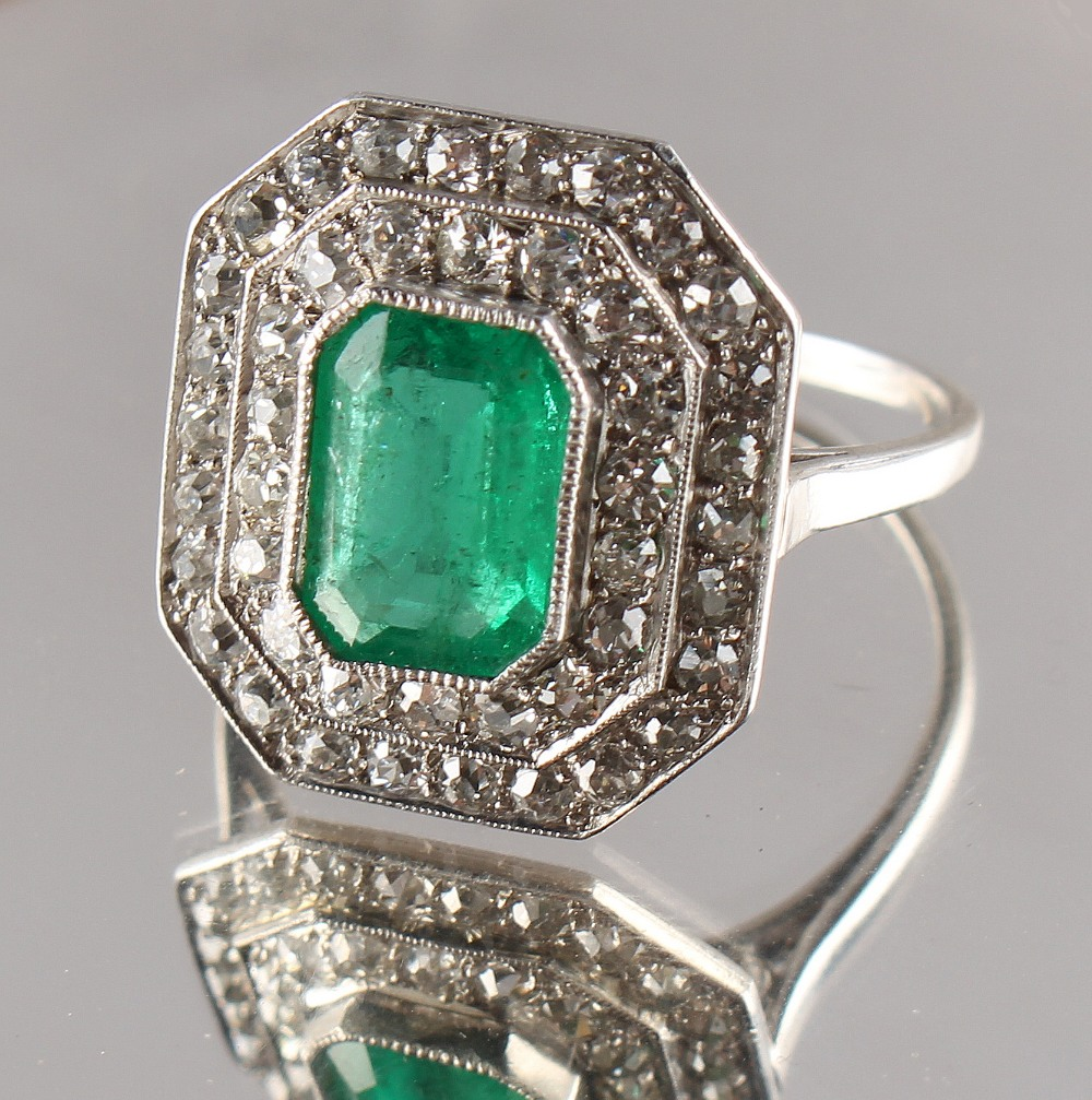 Lot 257 - An Art Deco emerald & diamond cluster ring, the octagonal cut Colombian emerald weighing an