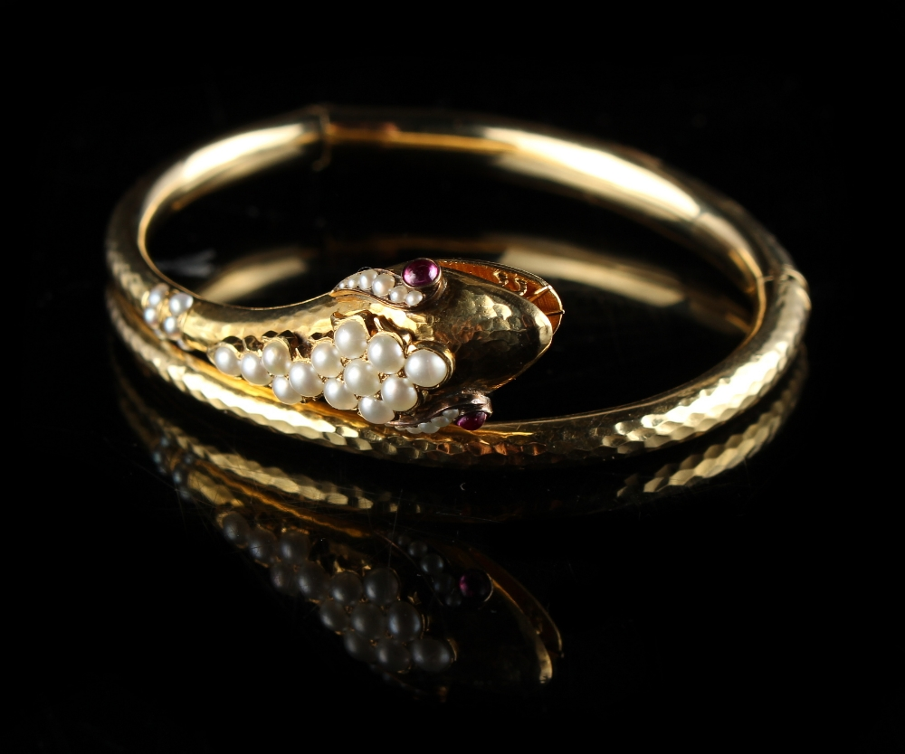 Lot 264 - A Victorian yellow gold snake bangle, circa 1870, set with ruby eyes & seed pearls, approximately