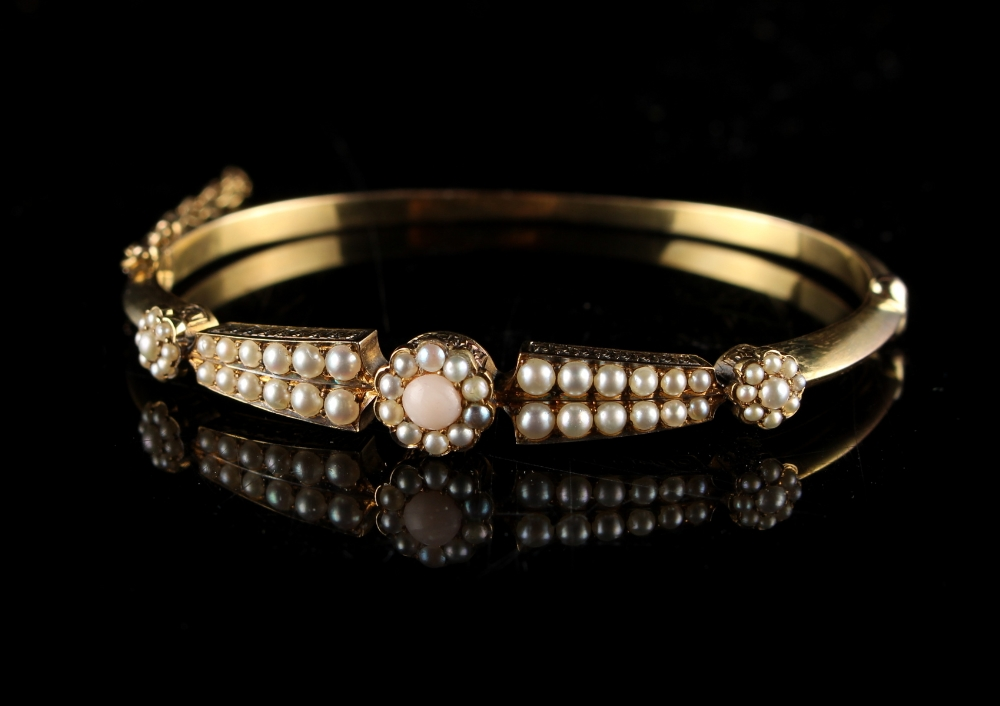 Lot 241 - A late 19th / early 20th century yellow gold coral & seed pearl hinged bangle, with safety chain, in